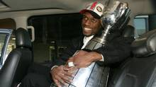 Edmonton Eskimos' wide receiver Ed Hervey holds the Grey Cup after arriving at the Edmonton International Airport on Monday, November 17, 2003. (The Canadian Press)