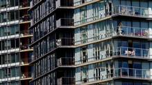 A woman sunbathes on the balcony of a condo in Vancouver, B.C. (DARRYL DYCK/THE CANADIAN PRESS)
