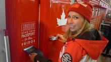 Tonia Hammer, Molson Coors social media manager, demonstrates how to open the Molson Canadian beer fridge with a Canadian passport at the Canada Olympic House in Sochi on Sunday, Feb. 16, 2014. (Neil Davidson/THE CANADIAN PRESS)
