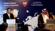 Canadian Foreign Minister John Baird, left, listens during a press conference with his Bahraini counterpart Sheik Khalid bin Ahmed Al Khalifa, right, in Manama, Bahrain, on Wednesday, April 3, 2013. A Canadian Press analysis found that exports of Canadian-made weapons to Bahrain increased by 100 per cent from 2011 to 2012. (Hasan Jamali/AP)