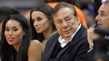 The NBA is investigating a report of an audio recording in which a man purported to be Los Angeles Clippers owner Donald Sterling, right, makes racist remarks while speaking to V. Stiviano, left. (Mark J. Terrill/Associated Press)