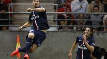 Zlatan Ibrahimovic of Paris St Germain jumps as he celebrates his goal with team mate Edison Cavnni during their French Ligue 1 soccer match against Reims at the Gustave Delaune Stadium in Reims August 8, 2014. (PASCAL ROSSIGNOL/REUTERS)