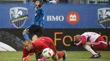 New York Red Bulls goal keeper Luis Robles and Aurelien Collin, right, react as Montreal Impact's Matteo Mancosu celebrates after scoring during the second half of Sunday's semi-final. (Graham Hughes/THE CANADIAN PRESS)