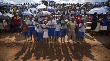 Rwandan children wait for a torch ceremony where hundreds gathered for the arrival of a small flame of remembrance and to hear genocide memories, at the Petit Seminaire school in Ndera, east of the capital Kigali, in Rwanda April 3, 2014. (Ben Curtis/Associated Press)