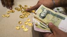 A customer buys Iranian gold coins at a currency exchange office in Tehran's business district in this photo from 2011. (RAHEB HOMAVANDI/REUTERS)