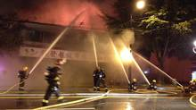 Fire fighters battle a blaze in East Vancouver, September 21, 2012. (ANDREA WOO/The Globe and Mail)