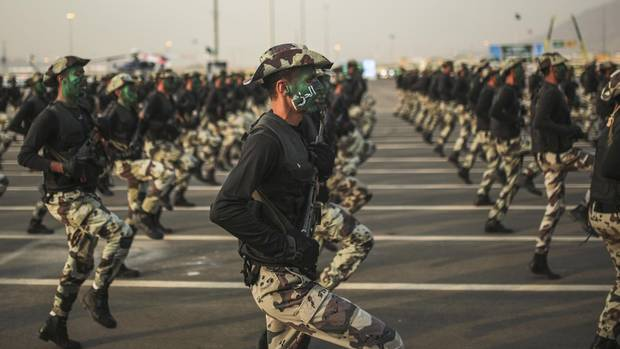 "In this Sept. 17, 2015, file photo, Saudi security forces, whose faces display the word ""Decisive"" take part in a military parade in preparation for the annual Hajj pilgrimage in Mecca, Saudi Arabia. (Mosa'ab Elshamy/AP)"