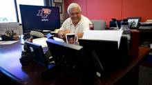 B.C. Lions' General Manager Wally Buono smiles as he looks over family photographs in his office at the team's facility in Surrey, B.C., on Wednesday August 15, 2012. (DARRYL DYCK For The Globe and Mail)