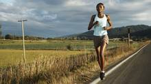 Woman running along rural road (Thomas Northcut/Stock photo | Getty Images | Photodisc)