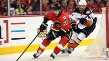 Michael Frolik of the Flames moves the puck around Shea Theodore of the Ducks during Game 4 of their playoff series in Calgary on Wednesday night. (Candice Ward/USA Today Sports)