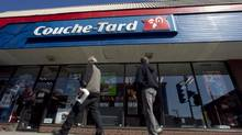 Pedestrians walk past a Couche-Tard convenience store in Montreal, April 18, 2012. (CHRISTINNE MUSCHI/REUTERS)
