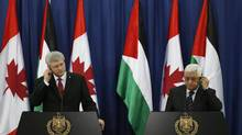 Prime Minister Stephen Harper, left, and Palestinian President Mahmoud Abbas adjust their ear pieces during a joint news conference in the West Bank city of Ramallah on January 20, 2014. (DARREN WHITESIDE/REUTERS)
