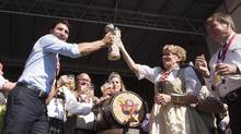 Prime Minister Justin Trudeau celebrates with Premier Kathleen Wynne after tapping the keg at the opening ceremony for Oktoberfest in Kitchener, Ont., on Friday, Oct. 7, 2016. (Hannah Yoon/THE CANADIAN PRESS)