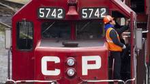 Canadian Pacific Rail workers stand on a locomotive at the company's Port Coquitlam yard east of Vancouver, B.C., in this file photo. (DARRYL DYCK/THE CANADIAN PRESS)
