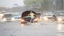 A woman checks her car in flood water during a storm in Toronto on Monday, July 8, 2013. (THE CANADIAN PRESS)
