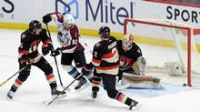 Ottawa Senators' Cody Ceci (5) and Dion Phaneuf (2) defend against Colorado Avalanche's Gabriel Landeskog (92) as a shot goes off the goal post beside Senators goalie Andrew Hammond during first period NHL hockey action in Ottawa on Thursday, Feb. 11, 2016. (Sean Kilpatrick/THE CANADIAN PRESS)