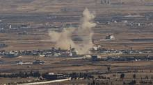 Smoke rises following an explosion in Syria's Quneitra province as Syrian rebels clashed with President Bashar al-Assad's forces, seen from the Israeli-controlled Golan Heights, Aug. 28, 2014. (Ariel Schalit/Associated Press)