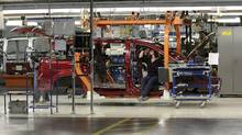 A Chrysler Group LLC employee inspects the frame of a Chrysler minivan as it moves down the production line at Chrysler Group's assembly plant in Windsor, Ontario, Canada, on Tuesday, Jan. 18, 2011. (Jeff Kowalsky/Bloomberg)