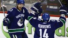 Vancouver Canucks' Daniel Sedin, left, of Sweden, and Alex Burrows celebrate Sedin's third goal of the game against the Calgary Flames during third period NHL hockey action in Vancouver, B.C., on Saturday April 10, 2010. (DARRYL DYCK/THE CANADIAN PRESS)