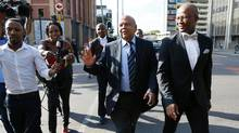 South African Finance Minister Pravin Gordhan, centre, arrives at the High Court in Pretoria, Gauteng province, on Thursday after being recalled from a trade trip by President Jacob Zuma. (PHIL MAGAKOE/AFP/Getty Images)
