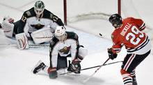 Chicago Blackhawks left wing Bryan Bickell scores past Minnesota Wild centre Mikael Granlund and goalie Niklas Backstrom during the first period of an NHL hockey game, Tuesday, March 5, 2013 in Chicago. (Associated Press)