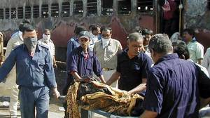Indian men carry a charred body of a train passenger in Gujarat, Feb. 27, 2002. A train carrying Hindu activists was set on fire, sparking further violence.
