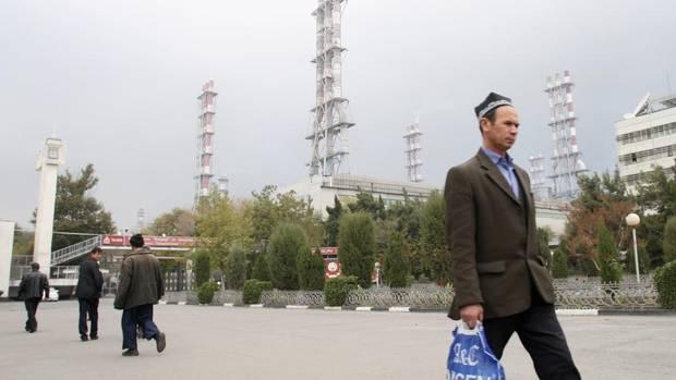 Employees walk past the Tajikistan Aluminium Co.'s aluminum smelter complex, known as Talco, in the town of Tursunzade on Nov. 19, 2012. (NOZIM KALANDAROV/REUTERS)
