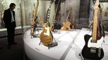 A 1963 Fender Telecaster Custom guitar belonging to John Lennon, right, is displayed in Paris in October, 2006. Fender Musical Instruments Corp. wants to sell about $150-million worth of stock. (Benoit Tessier/Reuters/Benoit Tessier/Reuters)