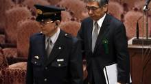 The Japanese government's nominee for Bank of Japan (BOJ) governor Haruhiko Kuroda (right) is led by a security officer as he arrives at a hearings session at the upper house of the parliament in Tokyo March 11, 2013. Kuroda said the central bank should focus on influencing market expectations because there is 'limited room' to lower interest rates further. (ISSEI KATO/REUTERS)