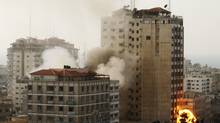 Smoke and fire are seen from an explosion by a high rise housing media organizations in Gaza City, Monday, Nov. 19, 2012. It's the Israel's military second strike on the building in two days. The Hamas TV station, Al Aqsa, is located on the top floor. (Hatem Moussa/AP)