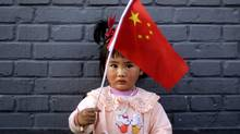 A young Chinese girl, plays with a Chinese flag while standing in an alley of Houhai district in Beijing Thursday. (Muhammed Muheisen/AP)