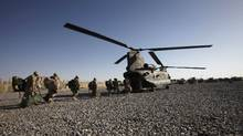 Canadian army soldiers board a CH-47 Chinook helicopter as they leave forward fire base Zangabad in Panjwai district in Kandahar province, southern Afghanistan, June 18, 2011. (Baz Ratner/Reuters)