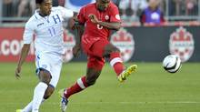 Canada's Julian de Guzman kicks the ball away from Honduras' Antony Lozano (L) during the first half of their World Cup qualifier match in Toronto June 12, 2012. (MIKE CASSESE/REUTERS)