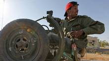 A rebel fighter jumps into a truck headed for the front lines near the city of Zintan in western Libya on June 13, 2011. (ANIS MILI/REUTERS)