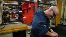 A worker is seen assembling an injection molding machine at a Husky Injection Molding Systems plant in Bolton, Ont., in a November 2005 file photo. (Fred Lum/The Globe and Mail)