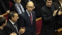 Ukrainian lawmakers applaud new Prime Minister Arseniy Yatsenyuk, center, during a session at the Ukrainian parliament in Kiev, Thursday, Feb. 27, 2014. (Sergei Chuzavkov/AP)