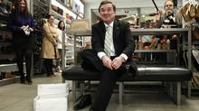 Canada's Finance Minister Jim Flaherty speaks to journalists while trying on his 'budget shoes' during a photo opportunity at a shoe store in Ottawa. (CHRIS WATTIE/CHRIS WATTIE/REUTERS)