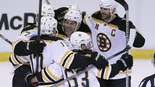 Boston Bruins right wing Jarome Iginla, centre, is mobbed by teammates as they celebrate their 3-2 overtime win in Game 4 of a first-round NHL hockey playoff series against the Detroit Red Wings in Detroit, Thursday, April 24, 2014. (Carlos Osorio/THE ASSOCIATED PRESS)