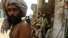An Indian sadhu (Hindu holy man) looks on as Indian paramilitary troops stands alert outside of a Hindu temple in Ayodhya on October 2, 2010. Schools, shops and businesses reopened in Ayodhya, Varanasi, Lucknow and other places with a mixed population of Hindus and Muslims while an Indian court ruled September 30 that a disputed holy site in Ayodhya with a history of triggering Hindu-Muslim clashes should be divided. (DIPTENDU DUTTA/AFP/Getty Images)