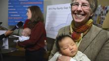 Midwife Mary Ann Leslie cradles six week old Emma Yang after a press conference about pay equity for midwives in Toronto on Nov. 27 2013. (FRED LUM/THE GLOBE AND MAIL)