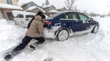 Residents of St. Thomas, Ontario push a snow bound car Sunday, Nov. 24, 2013, following a blast of wintry weather which dropped nearly 60cm if snow overnight. A snow squall pounded the region Saturday and into Sunday causing numerous accidents and closing Highway 401 Saturday for several hours due to a multi-vehicle crash. (Geoff Robins/THE CANADIAN PRESS)