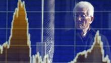 A man is reflected on the electronic board of a securities firm in Tokyo, Wednesday, Feb. 17. (Shizuo Kambayashi/AP)