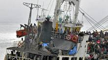 Tamil asylum-seekers crowd the deck of the MV Sun Sea off the coast of British Columbia in August. (MCpl Angela Abbey/DND/MCpl. Angela Abbey/DND)
