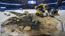 Construction workers hammer out concrete as they install the new dirt infield for the Toronto Blue Jays upcoming season at the Rogers Centre in Toronto on Wednesday, February 10, 2016. (Nathan Denette/THE CANADIAN PRESS)