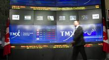 TMX Broadcast Centre manager Kris Backus walks in front of the centre's display board in Toronto. (Frank Gunn/Frank Gunn/THE CANADIAN PRESS)