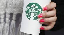 A woman holds a Starbucks takeaway cup in London Oct. 24, 2012. (SUZANNE PLUNKETT/REUTERS)