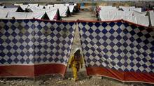 A women steps out through a gape between tents at a camp for flood-affected people in Sukkur, Pakistan on Tuesday, Aug. 31, 2010. Floodwaters that have devastated Pakistan for five weeks headed to the Arabian Sea on Tuesday after swallowing two final towns, but the challenges of delivering emergency aid to 8 million people remained. (Anjum Naveed/AP)