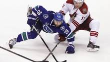 Vancouver Canucks' Chris Higgins fights for the puck with Phoenix Coyotes' Martin Hanzal during the second period of their NHL hockey game in Vancouver, British Columbia April 8, 2013. (BEN NELMS/REUTERS)