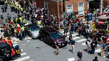People receive first-aid after a car accident ran into a crowd ofprotesters in Charlottesville, Va., on August 12, 2017. A vehicle plowed into a crowd of people Saturday at a Virginia rally where violence erupted between white nationalist demonstrators and counterprotesters, witnesses said. (PAUL J. RICHARDS/AFP/Getty Images)