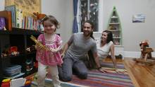 David Kaiser and Loree Tamanaha watch as their two-year-old daughter Olive plays in her Montreal home, Oct. 16, 2013. The family had difficulty finding daycare in their neighbourhood and have had to hire nannies for child care. (Christinne Muschi/The Globe and Mail)